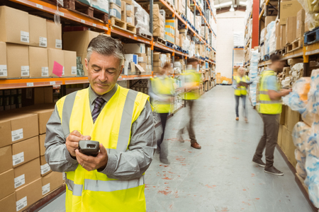 Photo pour Smiling male manager using handheld in a large warehouse - image libre de droit