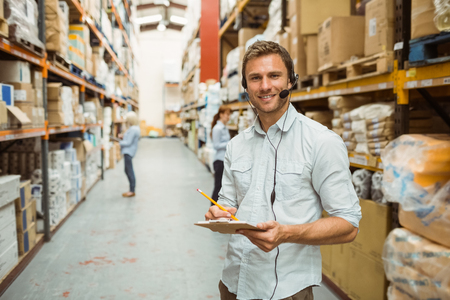 Photo for Warehouse manager wearing headset writing on clipboard in a large warehouse - Royalty Free Image