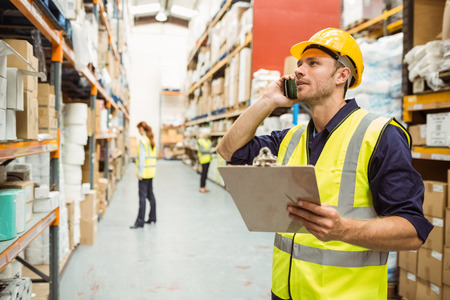 Photo pour Warehouse worker talking on the phone holding clipboard in a large warehouse - image libre de droit