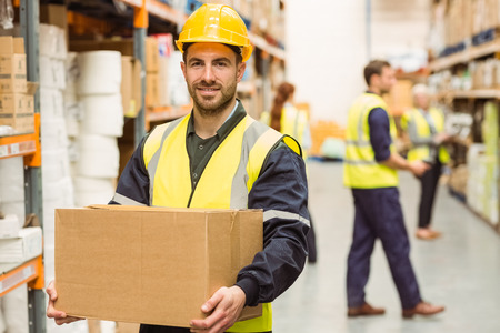 Photo for Warehouse worker smiling at camera carrying a box in a large warehouse - Royalty Free Image