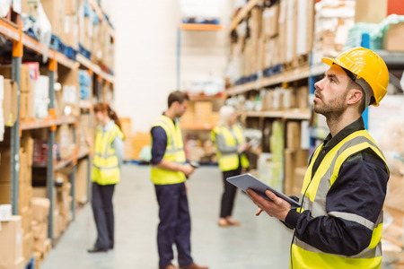 Foto de Focused warehouse manager writing on clipboard in a large warehouse - Imagen libre de derechos