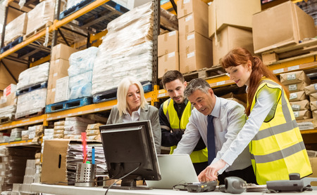 Photo pour Warehouse managers and worker talking in a large warehouse - image libre de droit