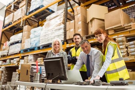 Foto de Warehouse team smiling at camera in a large warehouse - Imagen libre de derechos