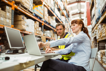 Photo pour Warehouse worker and manager looking at laptop in a large warehouse - image libre de droit