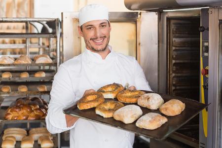 Foto de Happy baker showing tray of fresh bread in the kitchen of the bakery - Imagen libre de derechos