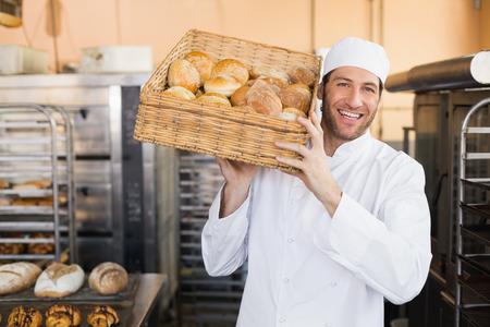 Foto de Baker holding basket of bread in the kitchen of the bakery - Imagen libre de derechos