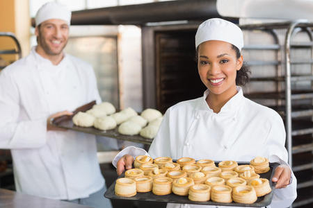 Foto de Baker smiling at the camera holding tray in the kitchen of the bakery - Imagen libre de derechos