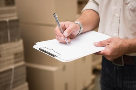Foto de Warehouse worker checking his list on clipboard in a large warehouse - Imagen libre de derechos