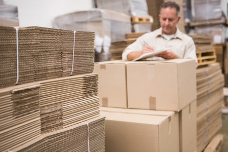 Photo pour Warehouse worker checking his list on clipboard in a large warehouse - image libre de droit