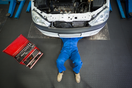 Photo pour Mechanic lying and working under car at the repair garage - image libre de droit