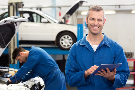 Photo pour Smiling mechanic using a tablet pc at the repair garage - image libre de droit