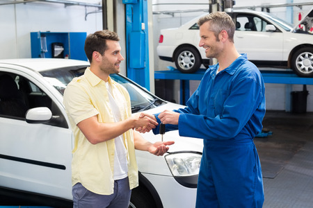 Photo pour Customer shaking hands with mechanic taking keys at the repair garage - image libre de droit