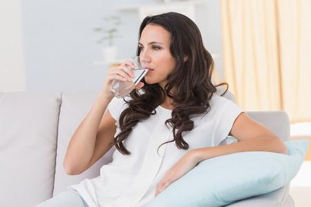 Foto de Pretty brunette drinking water on couch at home in the living room - Imagen libre de derechos