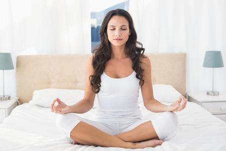 Foto de Calm brunette doing yoga on bed at home in bedroom - Imagen libre de derechos