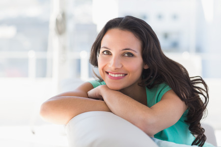 Photo for Pretty brunette relaxing on the couch at home in the living room - Royalty Free Image