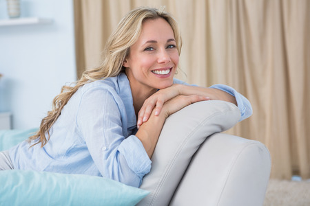 Foto de Cheerful pretty blonde sitting on couch at home in the living room - Imagen libre de derechos