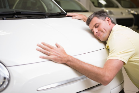Photo pour Smiling man hugging a white car at new car showroom - image libre de droit