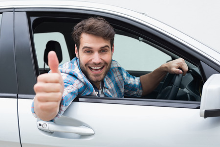 Photo pour Young man smiling and showing thumbs up in his car - image libre de droit