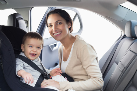 Photo for Mother securing her baby in the car seat in her car - Royalty Free Image