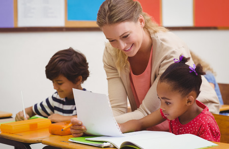 Photo for Pretty teacher helping pupil in classroom at the elementary school - Royalty Free Image