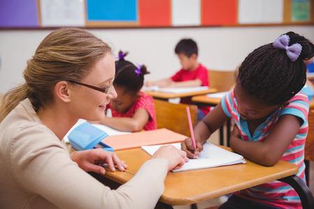 Foto de Cute pupil getting help from teacher in classroom at the elementary school - Imagen libre de derechos