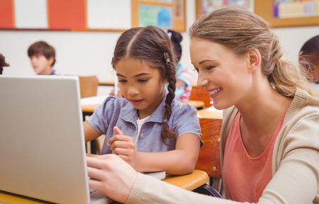 Foto de Cute pupil using computer with teacher at the elementary school - Imagen libre de derechos