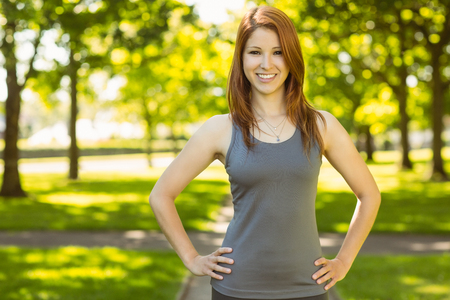 Foto de Portrait of a pretty redhead smiling on a sunny day - Imagen libre de derechos
