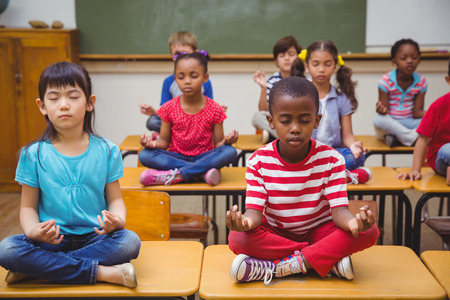 Foto de Pupils meditating in lotus position on desk in classroom at the elementary school - Imagen libre de derechos