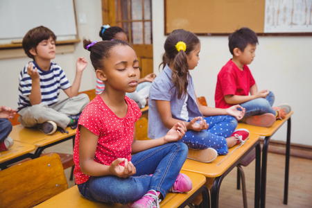 Photo pour Pupils meditating in lotus position on desk in classroom at the elementary school - image libre de droit