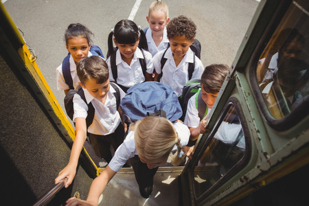 Photo pour Cute schoolchildren getting on school bus outside the elementary school - image libre de droit