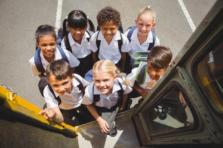 Photo pour Cute schoolchildren getting on school bus outside the elementary school - image libre de droit