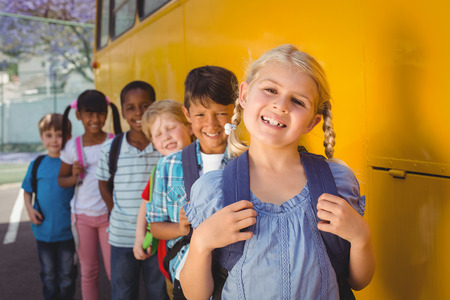 Photo pour Cute pupils smiling at camera by the school bus outside the elementary school - image libre de droit