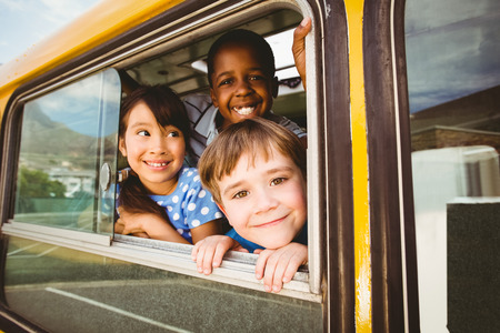 Foto de Cute pupils smiling at camera in the school bus outside the elementary school - Imagen libre de derechos