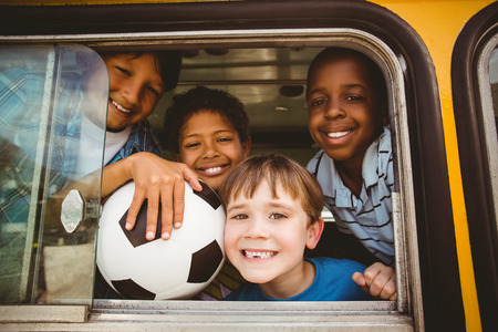 Photo pour Cute pupils smiling at camera in the school bus outside the elementary school - image libre de droit