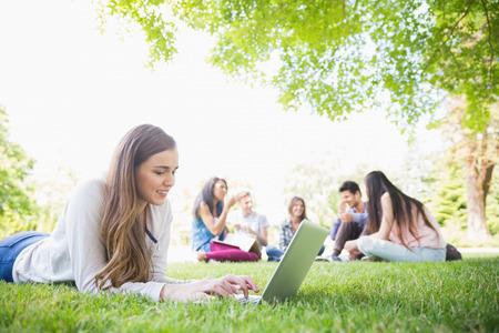Photo pour Happy student using her laptop outside at the university - image libre de droit