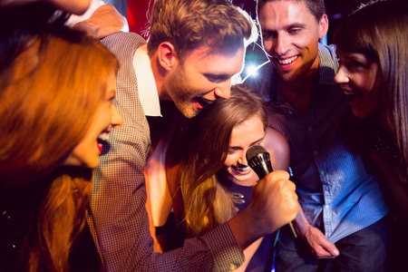 Photo for Happy friends singing karaoke together at the nightclub - Royalty Free Image