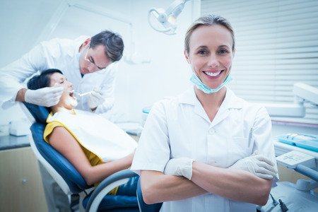 Foto de Portrait of smiling female dentist with assistant examining womans teeth in the dentists chair - Imagen libre de derechos