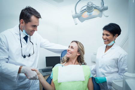 Photo for Male dentist with assistant shaking hands with woman in the dentists chair - Royalty Free Image