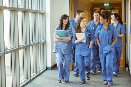 Photo for Medical students walking through corridor at the university - Royalty Free Image