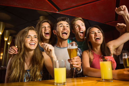 Happy friends drinking beer and cheering together in a bar