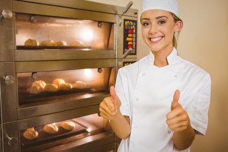 Foto de Baker smiling at camera beside oven in a commercial kitchen - Imagen libre de derechos