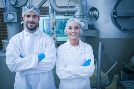 Photo for Food technicians smiling at camera in a food processing plant - Royalty Free Image