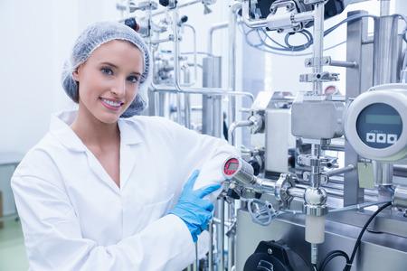 Photo for Smiling scientist leaning against gauge in the factory - Royalty Free Image