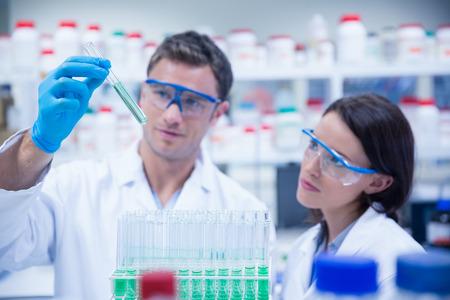 Foto de Smiling chemist holding test tube containing liquid in the laboratory - Imagen libre de derechos