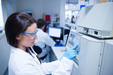 Foto de Young chemist using the machine in the laboratory - Imagen libre de derechos