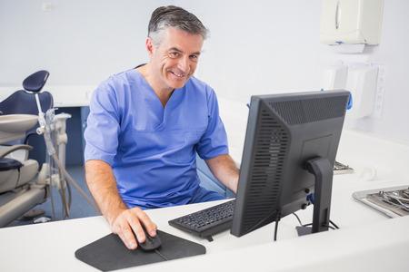 Foto de Portrait of a happy dentist using computer in dental clinic - Imagen libre de derechos