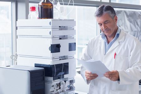 Foto de Scientist standing in lab coat reading analysis in laboratory - Imagen libre de derechos