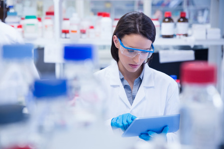 Photo pour Chemist wearing safety glasses and using tablet pc in lab - image libre de droit