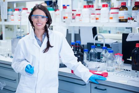 Foto de Portrait of a smiling chemist leaning against desk in the laboratory - Imagen libre de derechos