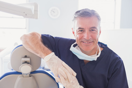 Photo for Smiling dentist leaning against dentists chair in dental clinic - Royalty Free Image
